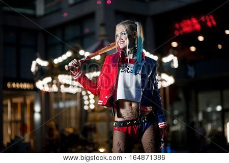 Smiling cosplayer girl in costume Harley Quinn on background lights of night city. Cosplay poster