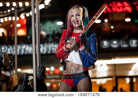 Portrait of smiling cosplayer girl in costume Harley on background lights of night city. Cosplay poster