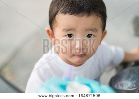 Close Up Of Asian Baby Boy Drinking Water With Straw.