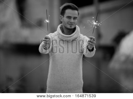 Young man with sparklers. He holds the sparklers in his hands.