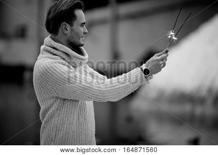 Young man with sparklers. He holds sparklers in his hands.