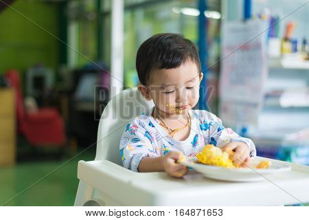 Asian Kid Eating Birthday Cake With Cream On Face.