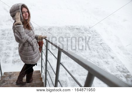 walk around the city: the girl has turned back and has looked at the camera, coming downstairs in the winter in a gray short fur coat
