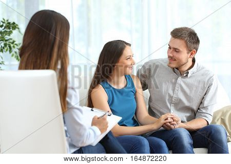 Happy couple listening to a marriage counselor and looking each other during therapy at home