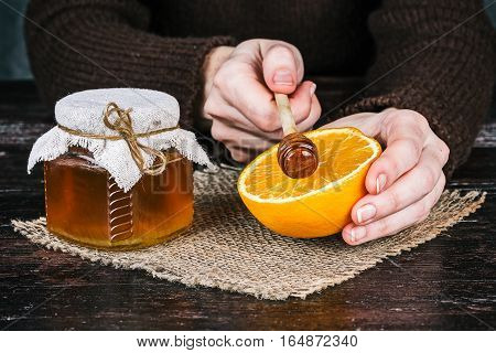 Human hands holding honey dipper and half of orange. Front closeup view
