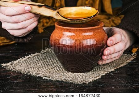 Human hands holding big wooden spoon of honey over clay pot. Front closeup view