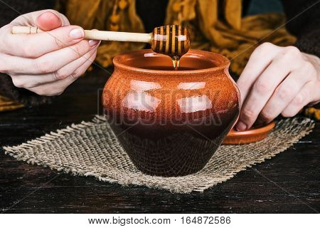 Human hands holding honey dipper over clay pot. Front closeup view