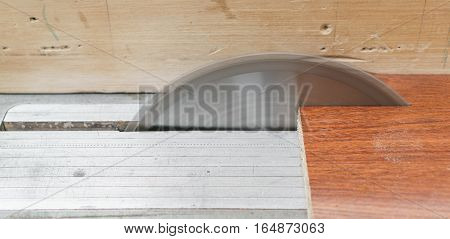Closeup of carpenter saw working with wood pieces