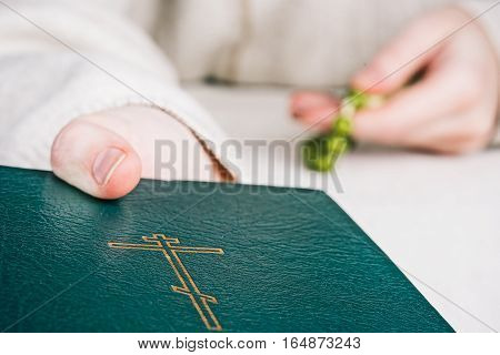 Closed holy bible with orthodox cross and rosary in human hands. Closeup front view
