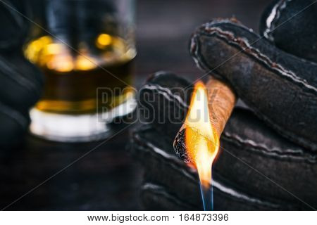 Human hands in winter gloves holding cigar and glass of whiskey. Someone outside lighting up the cigar. Closeup front view