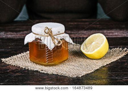 Honey jar and half of lemon.  Front closeup view