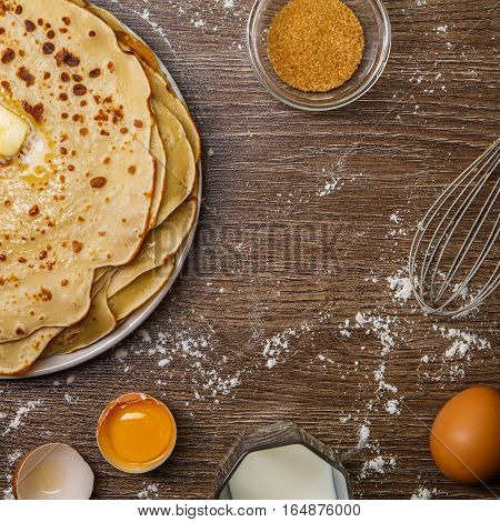 Flapjack on table with flour, eggs and whisk
