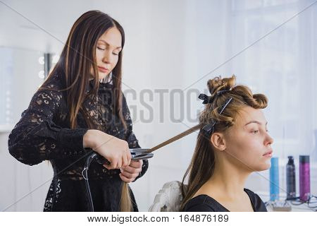Long hair being straightened with iron by stylist, beauty consept