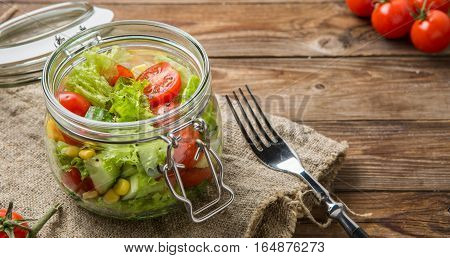 Summer salad of fresh vegetables on wooden table with fork, napkin and tomatoes
