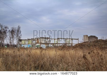 Ruined building remains in the field of a dry autumn grass with overcast sky