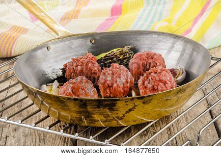 raw meat balls with a herbal mixture and garlic in a brass pan on cooling rack