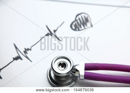 Stethoscope with cardiogram lying on desk in hospital.