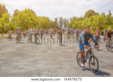 A blurred group of cyclists organized a summer arrival on bikes on the road. The concept of a healthy lifestyle and sports.