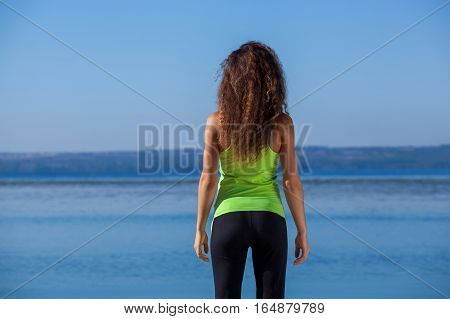 Young slim girl in black and light green sports suit sitting after jogging walks on the beach. The concept of a healthy lifestyle and body care.