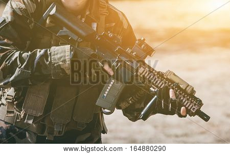 The soldier in the performance of tasks in camouflage and protective gloves holding a gun. The zone of military operations.