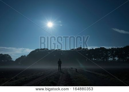 Silhouette Of Young Man Standing On Rural Road At Night.