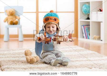 Happy kid boy playing with toys airplane