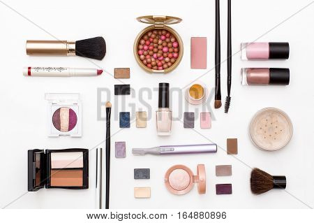 cosmetics for facial makeup: brushes powder lipstick eye shadow nail Polish trimmer and other accessories on white background top view. beauty flat lay concept