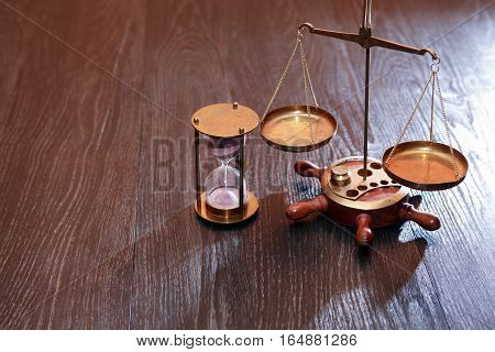 Vintage still life. Weight scale and hourglass on wooden background
