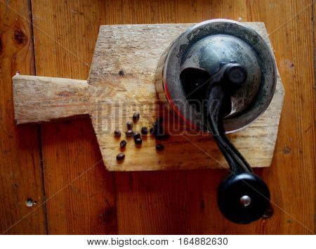 Vintage top view of coffee, pepper or sugar grinder or mill with a mechanical rustic handle on wooden board on wooden kitchen table