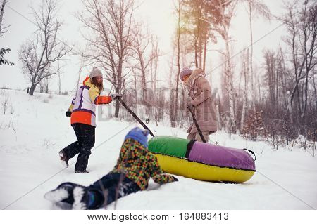 Group of happy cheerful people sliding on snow tubing. Two women and child having fun on hill. Winter vacation.