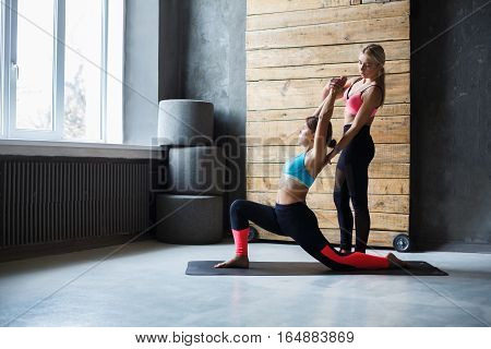 Yoga instructor helps beginner to make asana exercises. Teacher assists to make warrior pose, Virabhadrasana. Healthy lifestyle in fitness club. Stretching with coach
