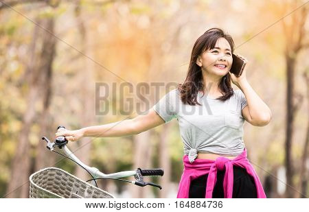 Attractive woman taking with phone while ride bicycle in countryside road lifestyle concept vintage tone