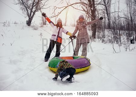 Happy cheerful people having fun on snow hill. Two women and child sliding on tubing. Winter vacation.