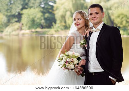 He is a winner. Horizontal soft focus portrait of a gorgeous newlywed couple posing near the lake