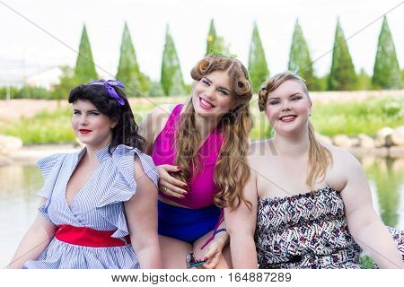 Three beautiful plus size models are sitting on the shore of the lake professional makeup and hairstyle