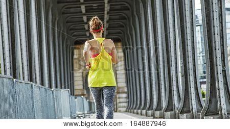 Active Woman Running On Pont De Bir-hakeim Bridge In Paris