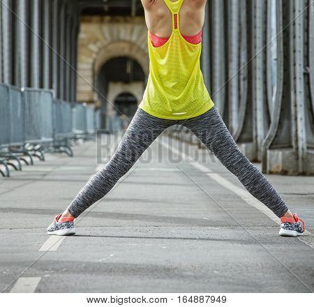 Outdoors fitness in Paris. Closeup on young healthy woman stretching on Pont de Bir-Hakeim bridge in Paris