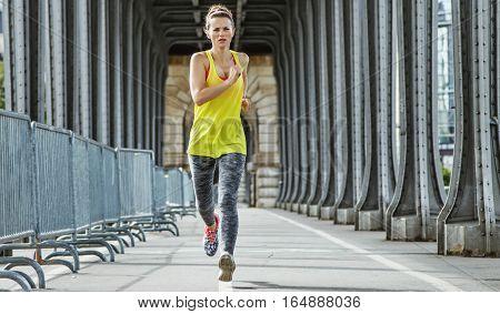 Active Woman Jogging On Pont De Bir-hakeim Bridge In Paris
