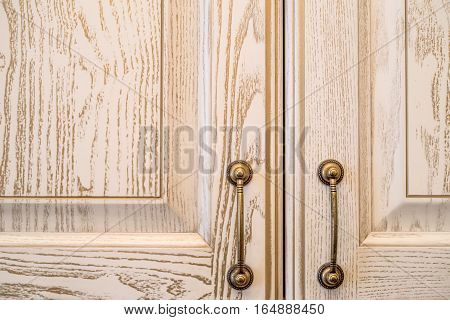 Close-up of vintage wooden kitchen cabinet or cupboard with metal handles as background.