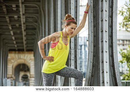 Outdoors fitness in Paris. young sportswoman relaxing after workout on Pont de Bir-Hakeim bridge in Paris