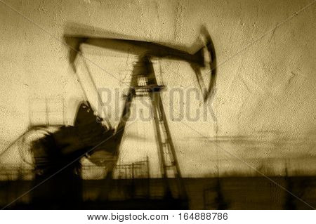 Work of oil pump jack on a oil field. Textured concrete grunge, blurred motion.  Concept oil and gas industry. Toned sepia.