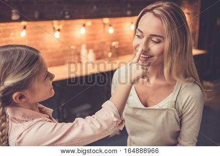 Cute little girl and her beautiful mom are having fun while baking in kitchen at home