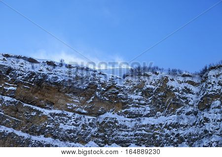 Rocks in snow at wind winter evening. View from ski slope. Greater Caucasus Shahdagh Azerbaijan.