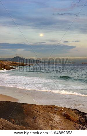 The moonrise over the Rio de Janeiro sea seen from the Arpoador stone in Ipanema