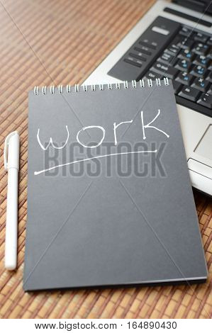 Workplace with a laptop and black notebook that says work.