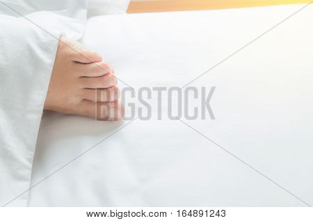 woman feet on the white bed over sun light