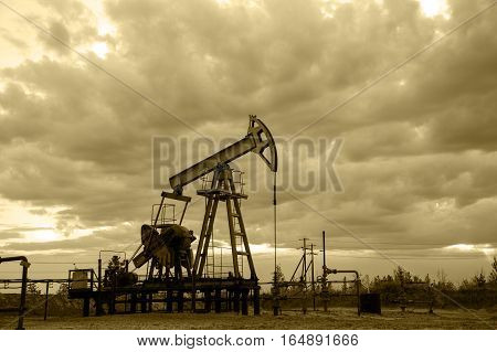 Oil pump jack and wellhead with valve armature during sunset on the oilfield. Oil and gas concept. Dramatic cloudy sky background. Toned sepia.