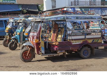 CHAMPASAK LAOS - NOV 23 : three wheel vehicle in pakse market important transportation hub in champasak distric southern of laos on november 23 2013