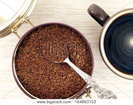 instant coffee in aluminum can and black coffee in a cup on wooden floor, closeup top view