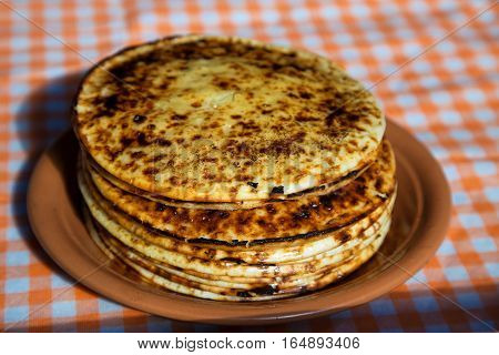 A stack of folded pancakes. Thick pancakes from the oven on a plate.
